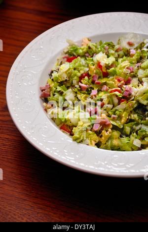 Blattsalat mit Schinken-Bits in einer Schüssel weiß - Stockfoto