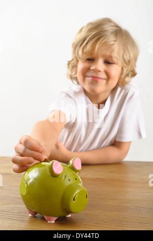 kleiner Junge legt eine Münze in sein Sparschwein - Stockfoto