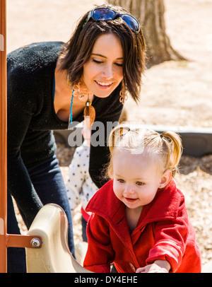 Schöne junge Mutter auf Park Spielplatz mit liebenswert, niedlich 16 Monate Baby Girl Spielen - Stockfoto