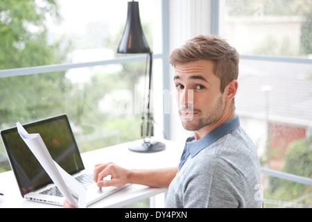 Man sitzt am Schreibtisch im Home Office - Stockfoto