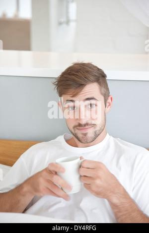 Mann, sitzend im Bett halten Mug - Stockfoto
