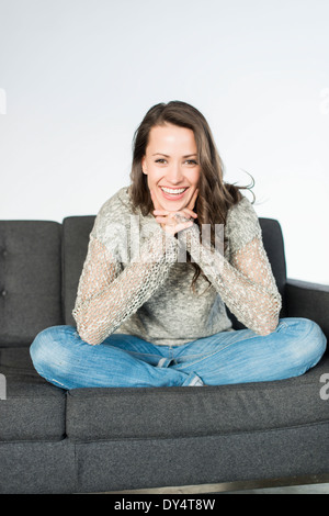 Frau sitzt auf dem Sofa - Stockfoto