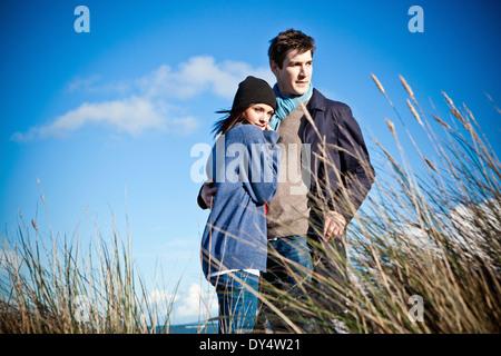Paar steht auf Sanddünen, Bournemouth, Dorset, Großbritannien - Stockfoto