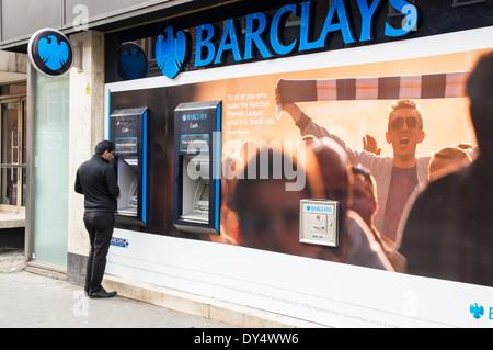 Ein Mann Bargeld von Barclays Geldautomaten in London England Vereinigtes Königreich Großbritannien - Stockfoto
