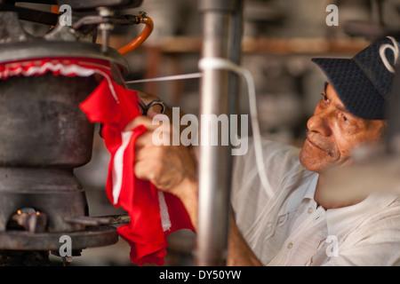 Hutmacher schneiden und stretching Stoff in Werkstatt - Stockfoto