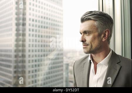 Porträt von reifer Geschäftsmann aus Bürofenster - Stockfoto