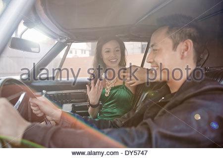 Glückliches Paar im Chat während der Fahrt im Auto - Stockfoto
