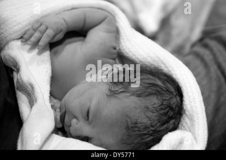 Schwarz / weiß Foto des neugeborenen Mädchen in eine Decke von Papa gewickelt - Stockfoto