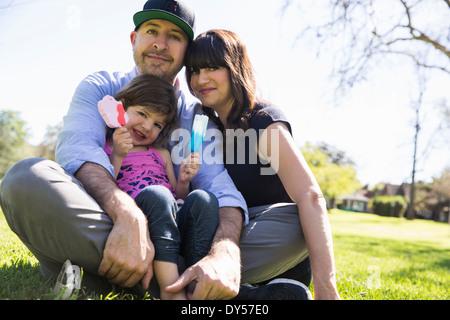 Porträt von Mitte erwachsenes paar und Tochter sitzen im park - Stockfoto