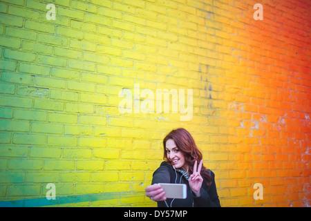 Junge Frau, die die Selbstporträt neben gelbe Wand - Stockfoto