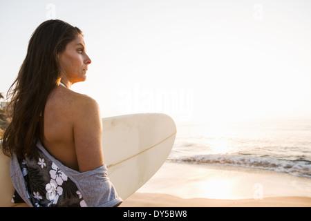 Surfer mit Surfbrett, Blick auf See - Stockfoto