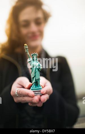 Junge Frau mit Freiheitsstatue Liberty Souvenir von Hudson River, New York, USA - Stockfoto