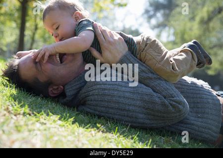 Vater und Sohn spielen auf Rasen - Stockfoto