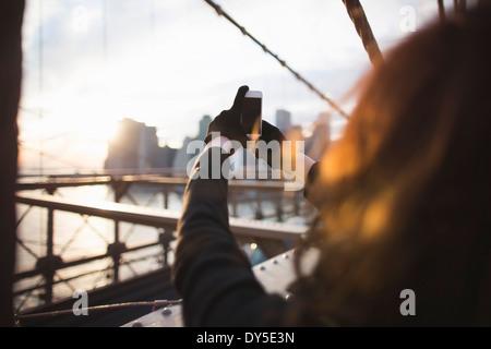 Junge Frau fotografieren Stadt auf Smartphone, New York, USA - Stockfoto