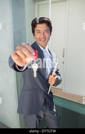 Zuversichtlich zeigt Haustürschlüssel stehenden Immobilienmakler - Stockfoto