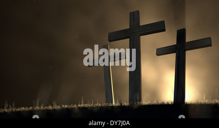 Ein Konzept der Kreuzigung mit drei Holzkreuze auf einem grasbewachsenen Hügel Hintergrundbeleuchtung durch einen - Stockfoto
