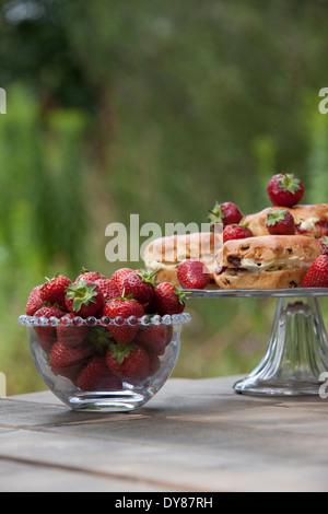 Erdbeeren in ein Glas Schüssel, Scones mit Sahne und Marmelade auf eine Kuchenplatte - Stockfoto
