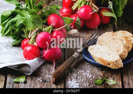 Frisches nass Radieschen mit Vintage Gabel, Meersalz und Brot über alten Holztisch