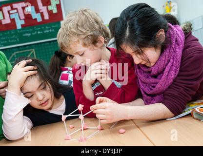 Nicht behinderte und behinderte Schüler (in diesem Fall ein Mädchen mit Down-Syndrom) lernen gemeinsam in der gleichen - Stockfoto