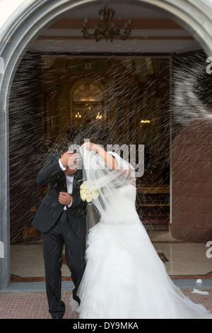 Die Braut und der Bräutigam erhalten Reis werfen Familienmitglieder aus der Kirche und Freunde am Tag ihrer Hochzeit - Stockfoto