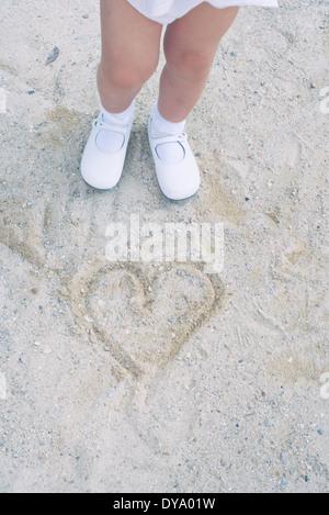 Kind stehend über Herz in Sand gezeichnet - Stockfoto