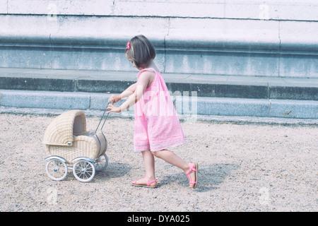 Kleines Mädchen Miniatur Kinderwagen schieben
