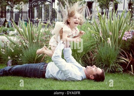 Vater liegen auf dem Rasen, spielerisch junge Tochter in die Luft heben - Stockfoto