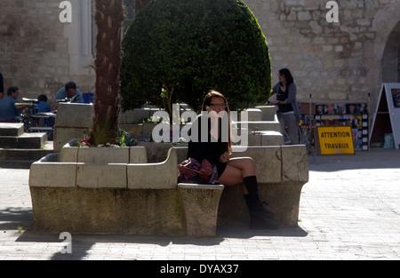Junge Frau am Telefon bei Sonnenschein auf Bank in der Stadt - Stockfoto