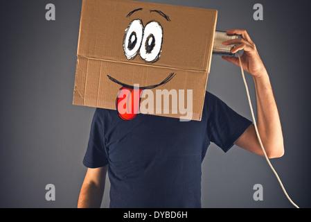 Mann mit Karton am Kopf mit Blechdose Telefon für ein Gespräch. Glückliches Gesichtsausdruck. - Stockfoto