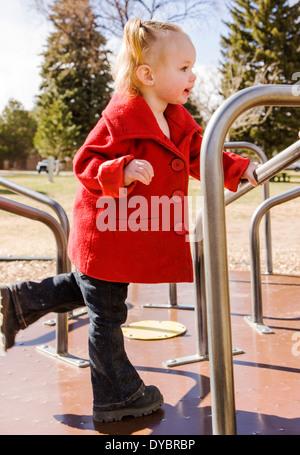 Niedlich, liebenswert 16 Monat kleine Mädchen spielen auf einem Spielplatz Park Karussell - Stockfoto