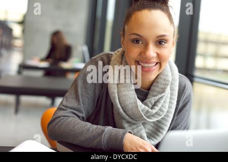 Nahaufnahme Portrait von junge afrikanische Frau sitzt in Bibliothek Blick auf die Kamera zu Lächeln. Studentin - Stockfoto