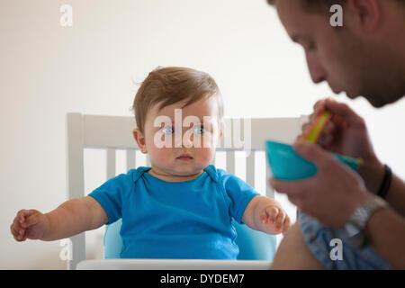 Baby Junge von seinem Vater gefüttert. - Stockfoto
