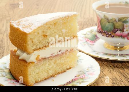 Ein Stück von Victoria Biskuit mit einem heißen Getränk serviert in einem Bone China Tasse und Untertasse - Stockfoto