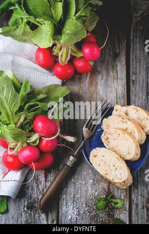 Frisches nass Radieschen mit Vintage Gabel, Meersalz und Brot über alten Holztisch. Ansicht von oben