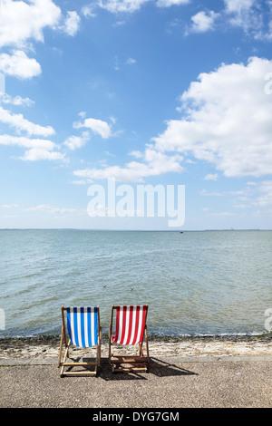 Zwei leere Liegestühle am Southend direkt am Meer. - Stockfoto