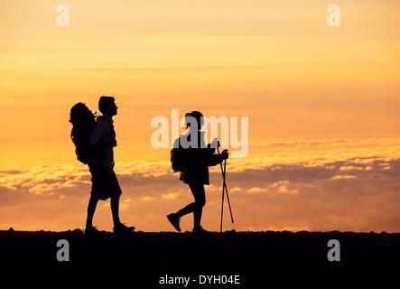 Silhouetten von zwei Wanderer mit Rucksack wandern bei Sonnenuntergang. Wandern und genießen den Sonnenuntergang - Stockfoto