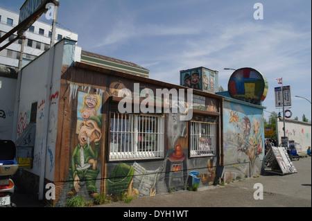 Blauer Himmel Schrägansicht Souvenir DDR Reisepass Stempeln Shop, mit Cartoons, gestrichene Wände, East Side Gallery, - Stockfoto
