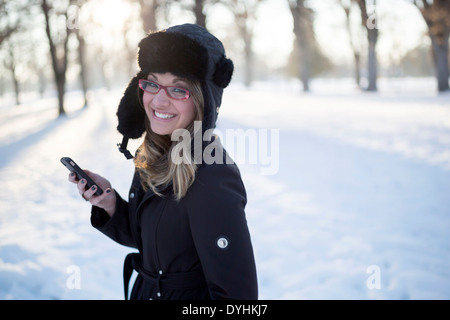 Eine gut gekleidete junge Frau lächelt wie sie mit ihrem Handy in einem Winter Park schlendert. - Stockfoto