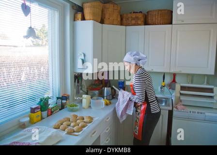 Frau in ihren 70ern Backen in kleinen Küche, Finnland, Europa - Stockfoto