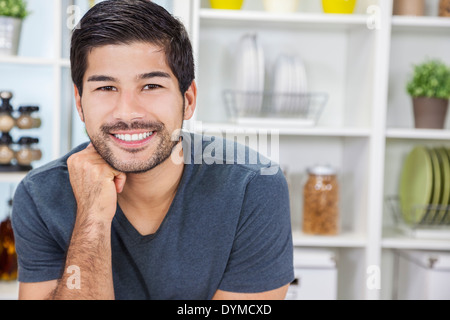Porträt der schönen lächelnden jungen asiatischen Mann mit einem Bart in einer Küche zu Hause - Stockfoto