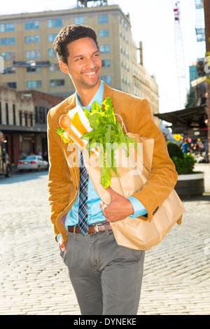 Gemischte Rassen Geschäftsmann mit Lebensmitteln auf Stadtstraße - Stockfoto