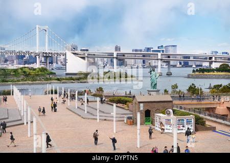 Freiheitsstatue auf der Insel Odaiba mit Regenbogen-Brücke im Hintergrund. Tokio, Japan. - Stockfoto