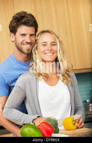 Glückliches junges Paar zu Hause in der Küche, Abendessen - Stockfoto
