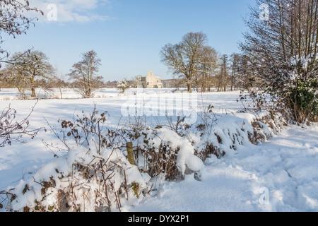 Hecken und Feldern im Schnee, in der Nähe von Pyrford, Surrey, UK, mit Ruinen der Newark Priory im Hintergrund - Stockfoto