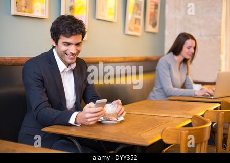 männliche fröhlich Restaurant Smartphone Café Nachricht sms - Stockfoto