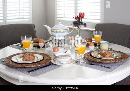Esstisch für Frühstück mit Brötchen, Eiern und Orangensaft in einem hell erleuchteten Raum schön gelegt - Stockfoto