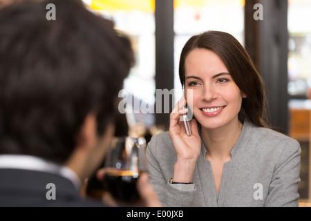 Weiblich männlich fröhlich Smartphone Abendessen bar - Stockfoto