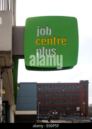 Ein Job Centre Plus Schild am Middleton Jobcenter, Greater Manchester, mit Warwick der stillgelegten Mühle im Hintergrund. - Stockfoto