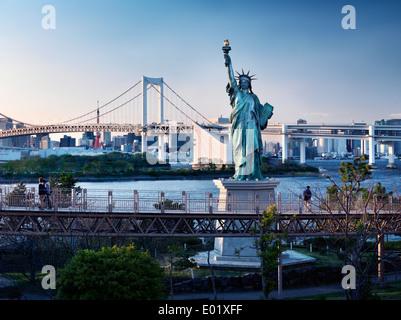 Freiheitsstatue mit Rainbow Bridge im Hintergrund in Odaiba, Tokio, Japan. - Stockfoto