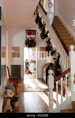 Weihnachtsschmuck hing von einer Treppe in einem Flur mit Holzdielen und verzweifelt suchen Bank - Stockfoto